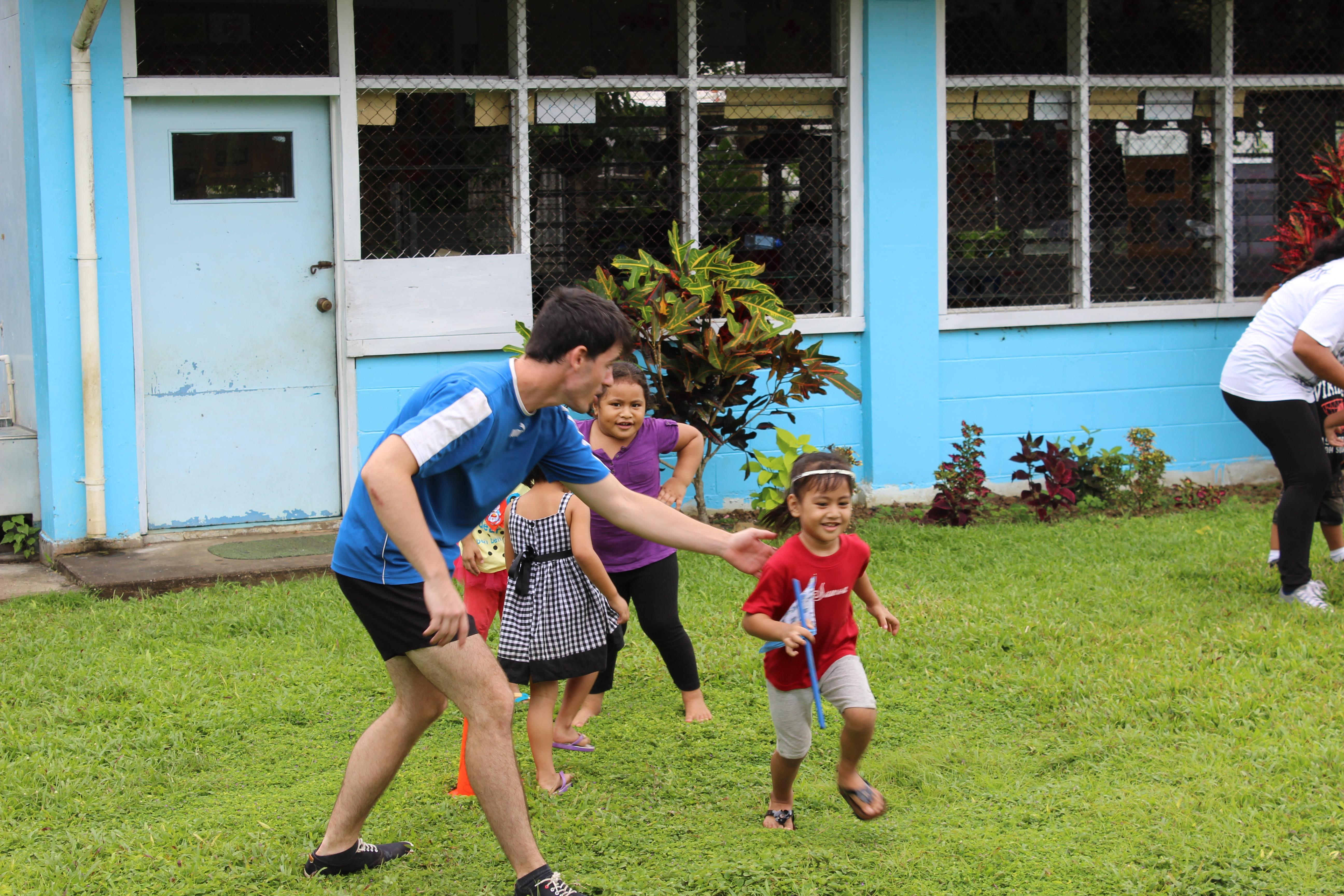 A student facilitates physical exercises as part of his volunteer rugby coaching in Samoa.